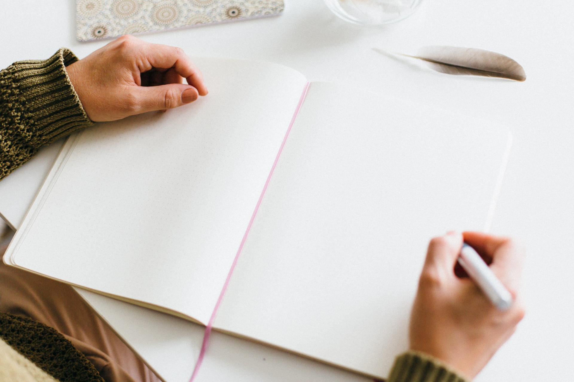 Ein offenes Notizbuch. Ich halte einen Füller in der Hand, bereit Inspirationen für wunderbare Gedanken to go aufzuschreiben.